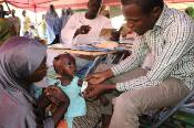 A baby's armed is measured in a mobile clinic to assess acute malnutrition.