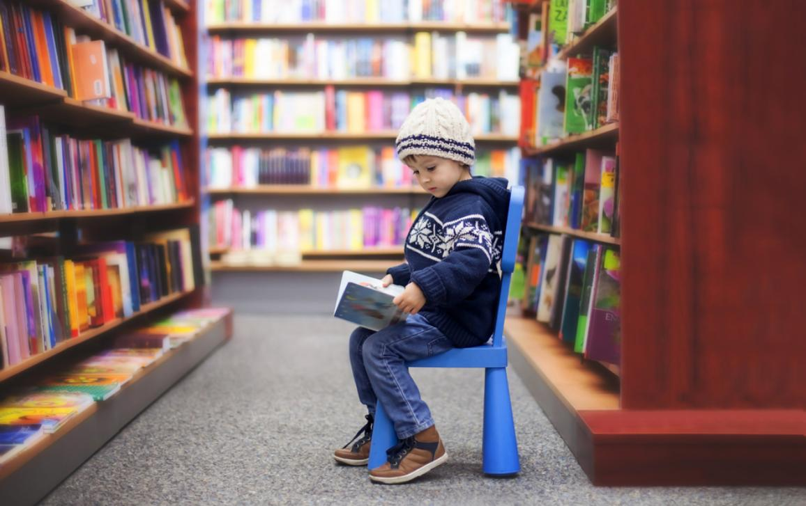Child sitting on a chair in a library, reading a book