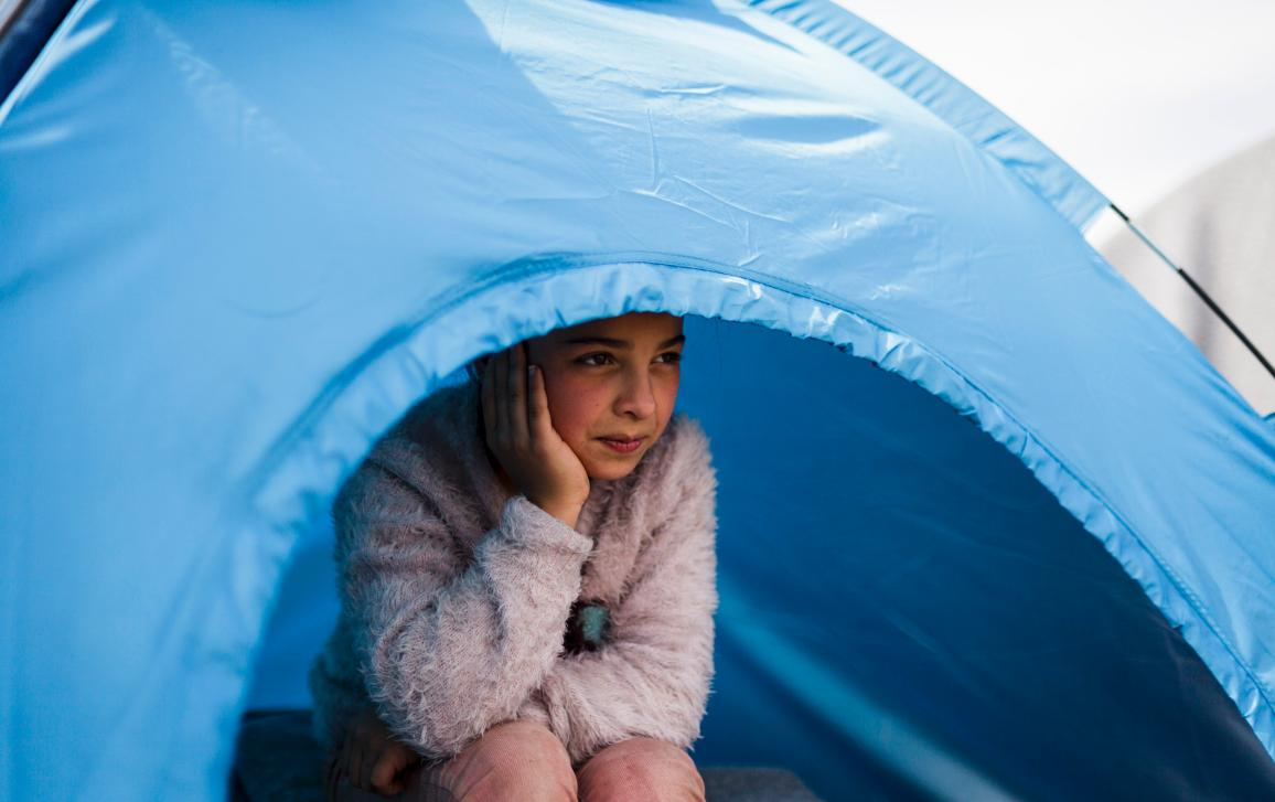 01_Migration: Adiba (11) sits inside the small camping tent she shares with her mother and her 4 siblings while the family waits at the Idomeni transit station to cross into the Former Yugoslav Republic of Macedonia. ©UNHCR/Achilleas Zavallis