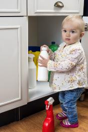 Little child playing with cleaning products at home