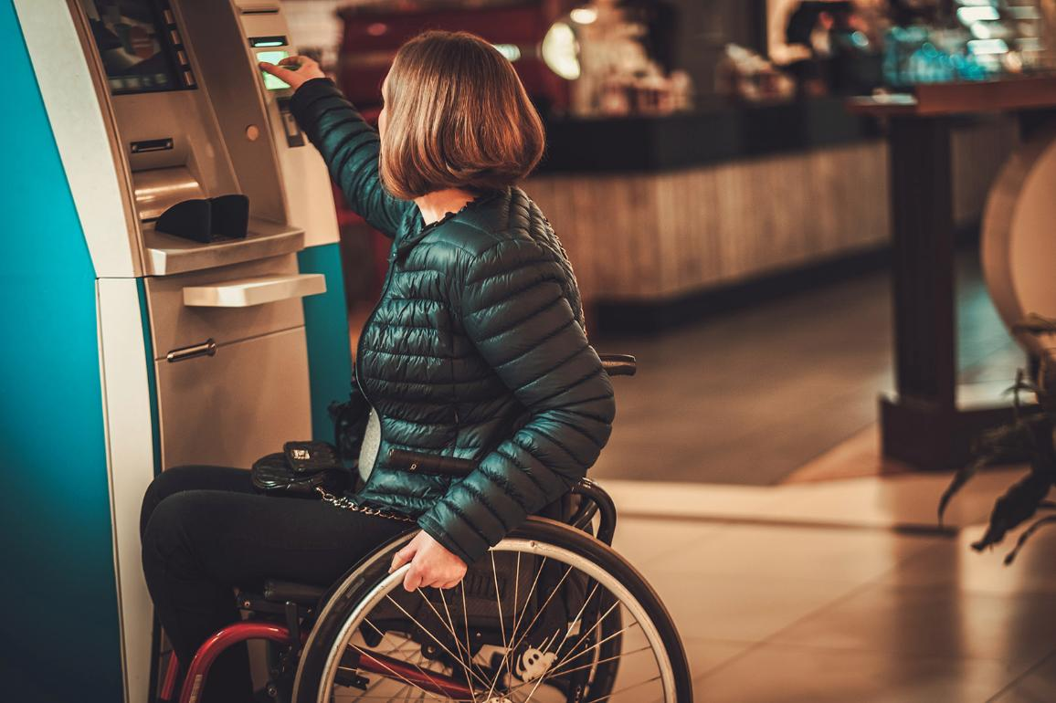 Vrouw in rolstoel bij geldautomaat