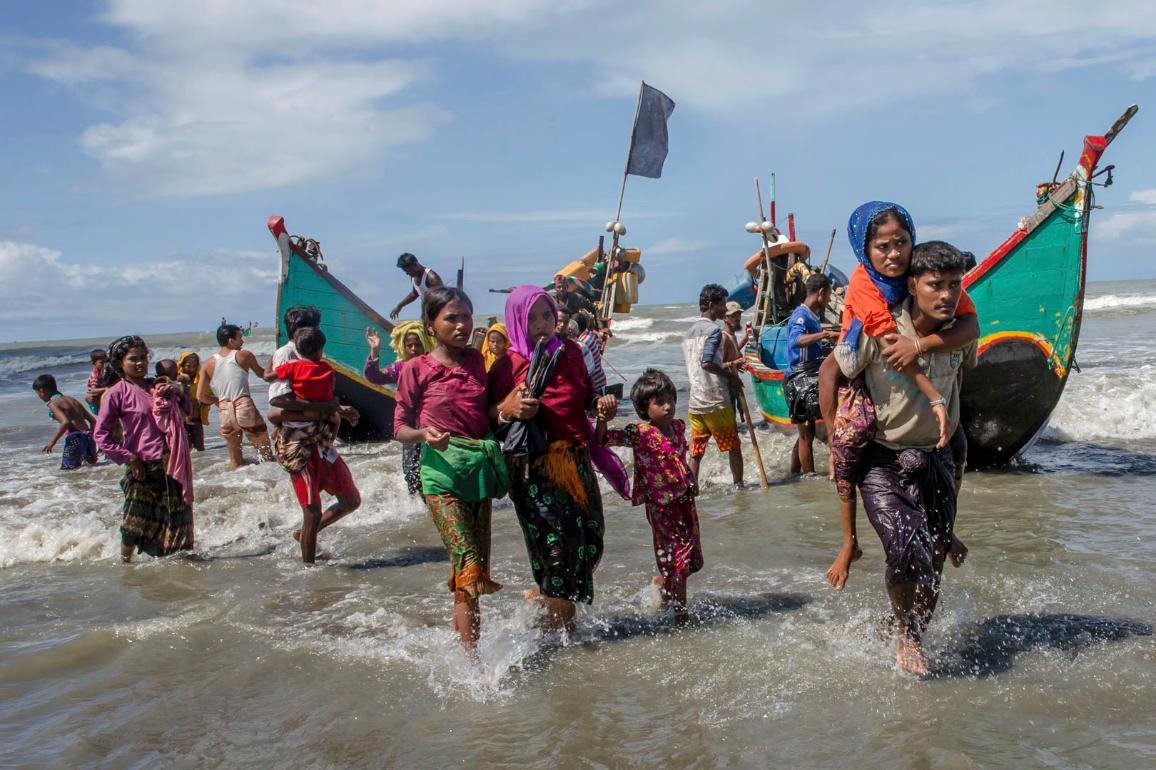 Dezenas de homens, mulheres e crianças à chegam a uma praia do Bangladeche a partir de barcos de madeira. ©Dar Yasin/AP Photos/European Union-EP