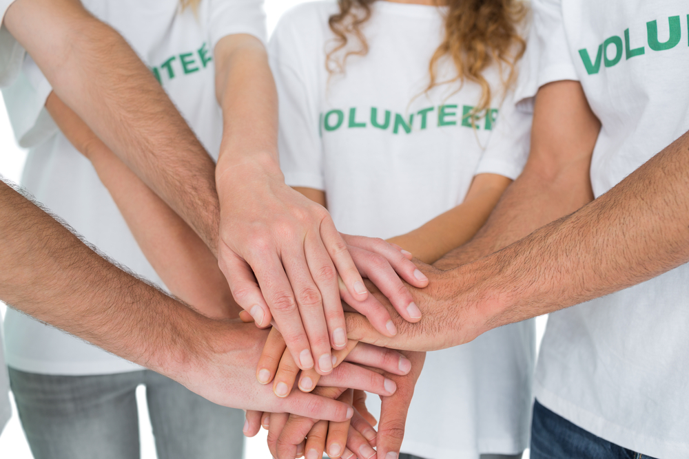 Close-up of volunteers with hands together over white background