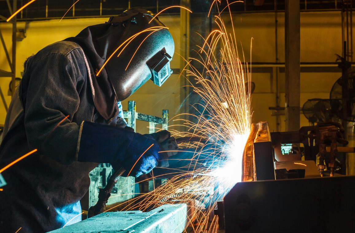A worker is welding in a car factory with sparks. ©AP Images/European Union-EP