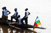 logboat on Oubangui river in Central African Republic with the country's flag