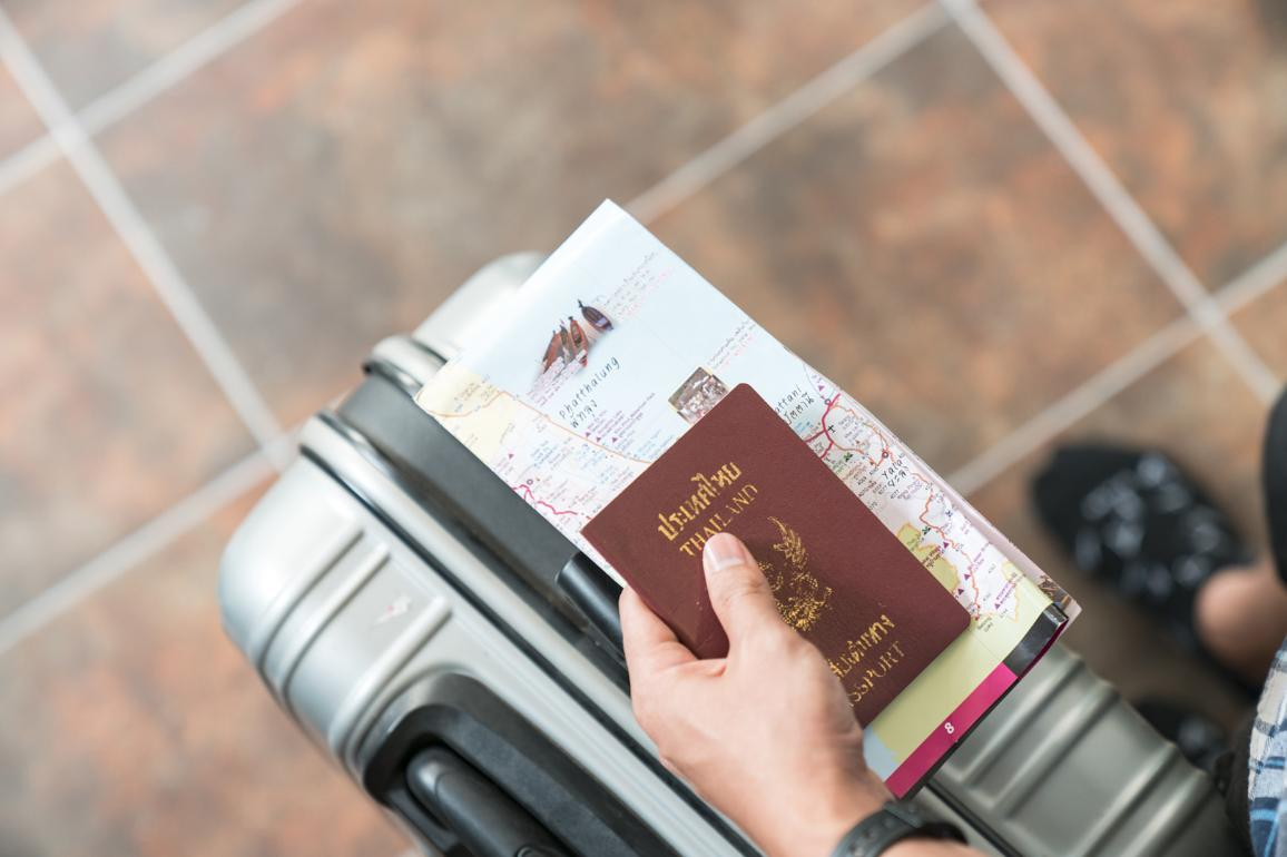 Hand holding passport at border control