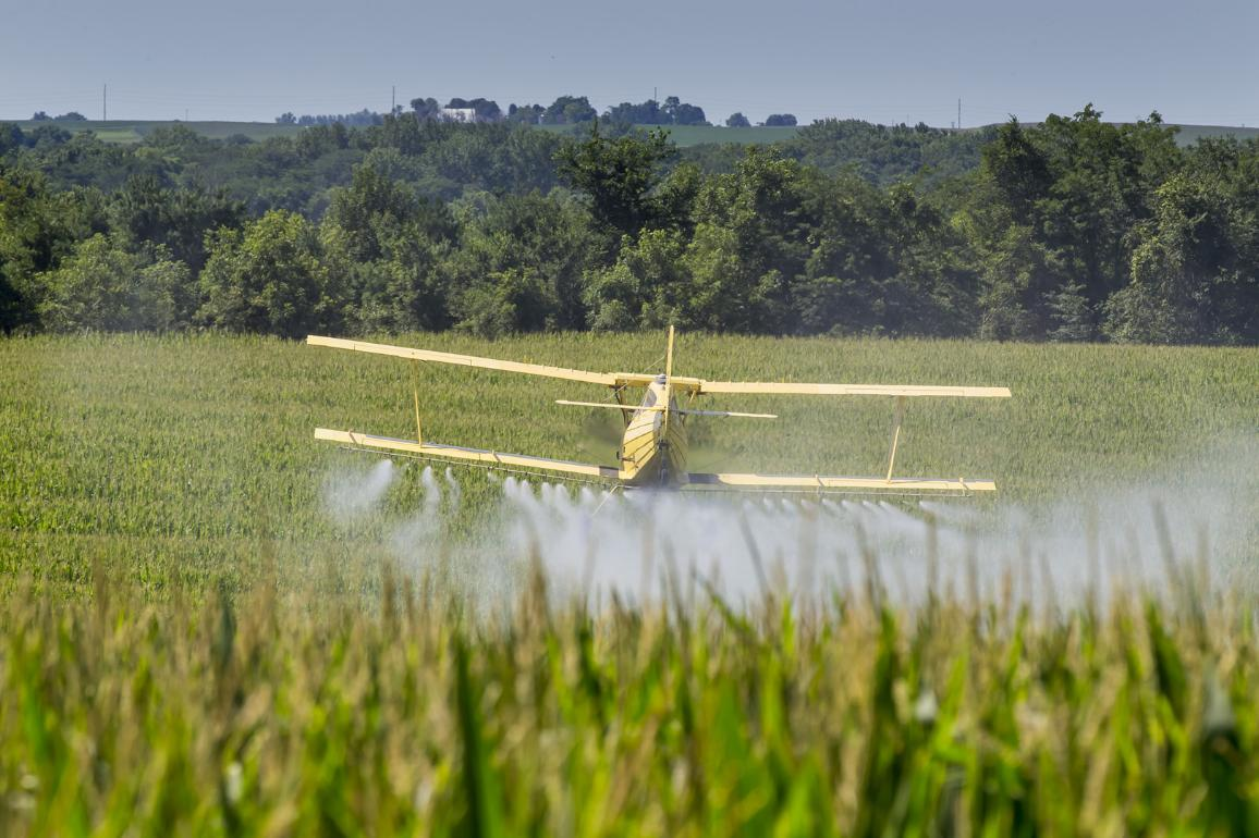 Yellow crop duster spraying pesticide