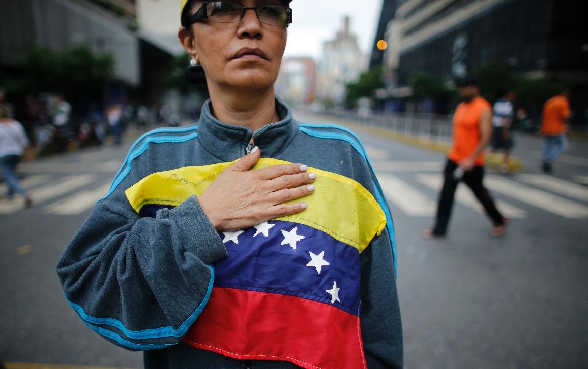Imagem de uma senhora com a mão no coração ©EP/AP Images/Ariana Cubillos