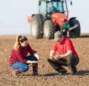 Young Couple of farmers with tractor
