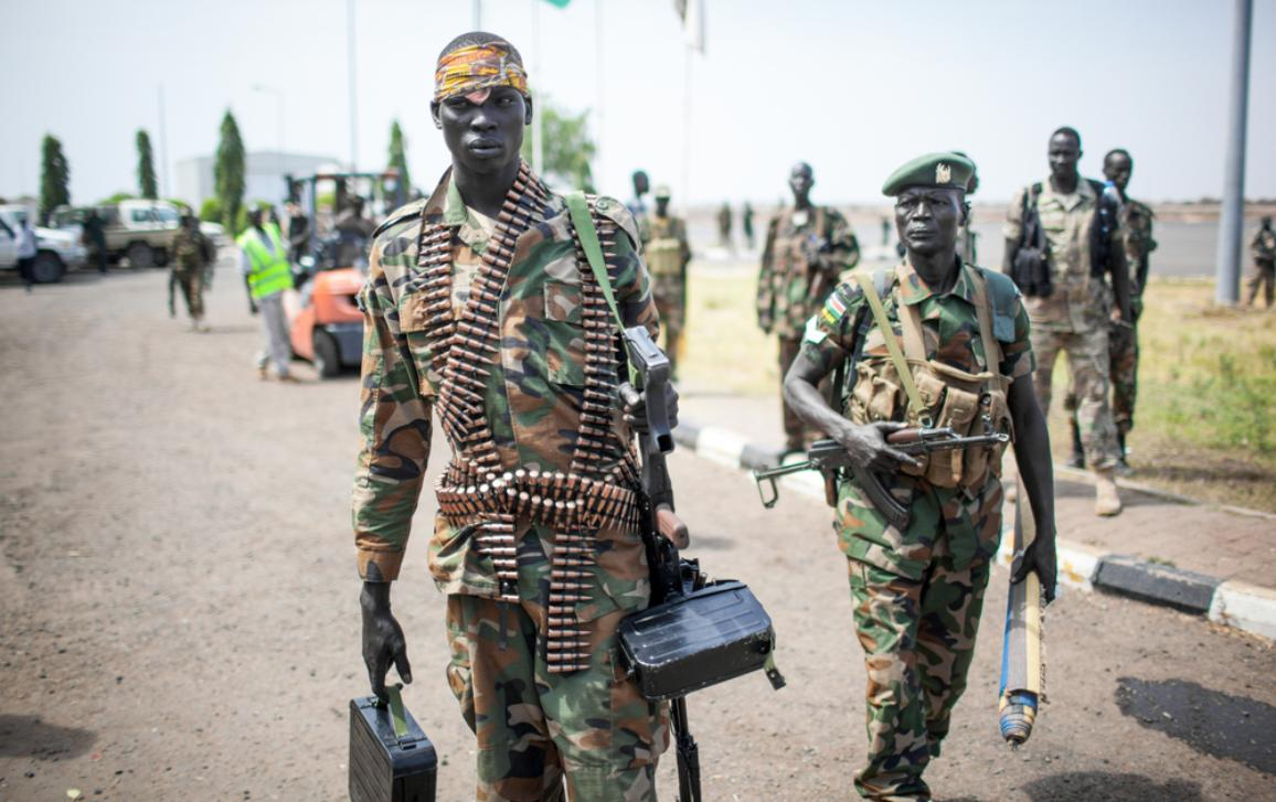 Military conflict in Africa showing soldier carrying a machine gun