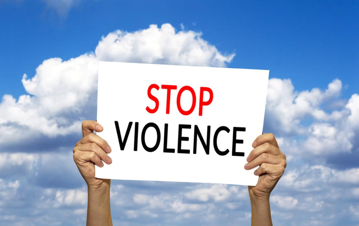 "Hands holding ""Stop Violence"" sign"