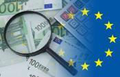 Euro notes, magnifying glass, calculator, EU flag