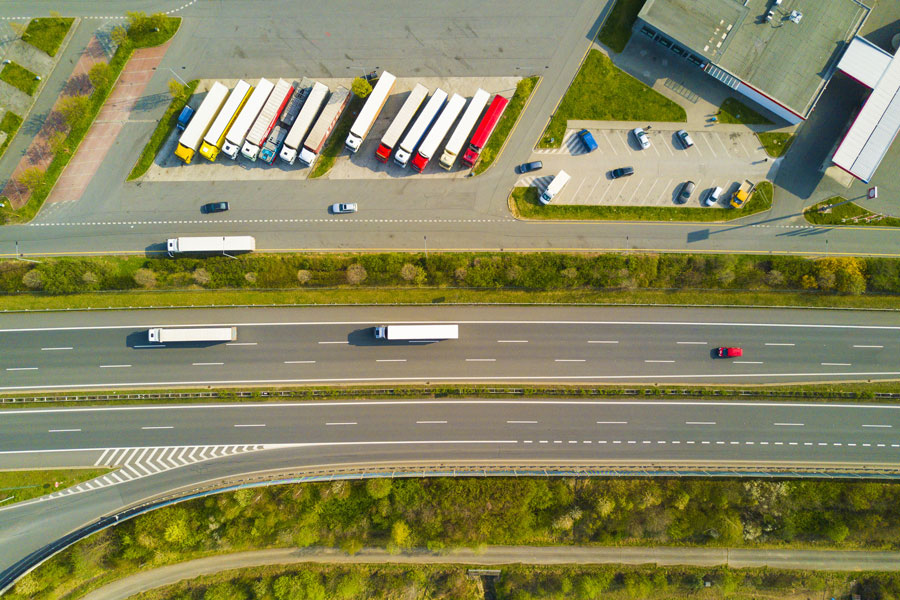 Trucks on motorway and on parking place seen from above