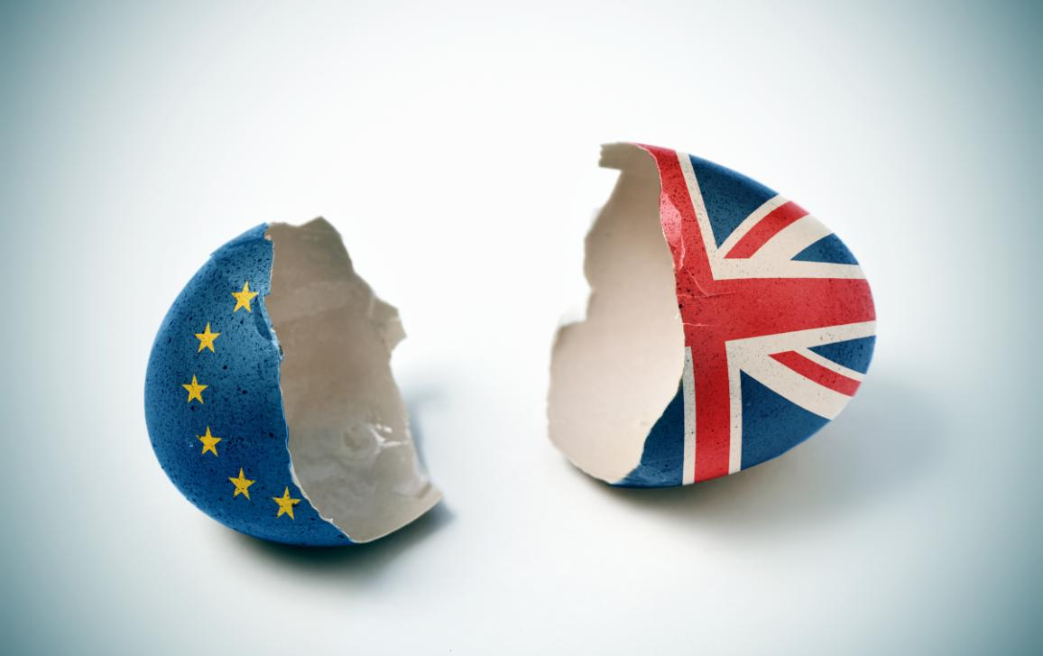 the two halves of a cracked eggshell, one patterned with the flag of the European Union and the other one patterned with the flag of the United Kingdom