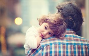 Child carried in arms by the father