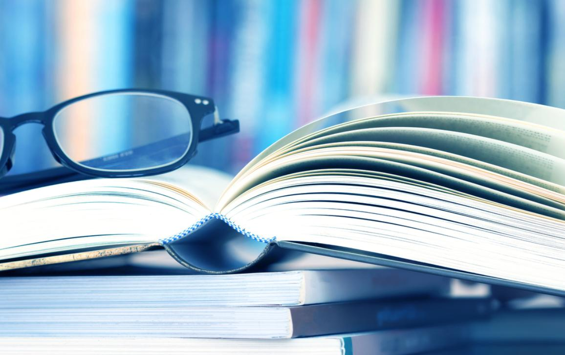 Photo of a pair of glasses on top of an open book.