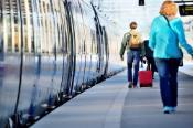 Two passengers walking along a train on a platform