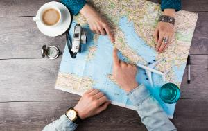 Couple planning holiday trip with map on table