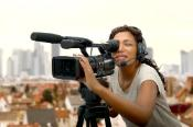 a young African American woman with professional video camera and headphone, standing outside with city skyline in background