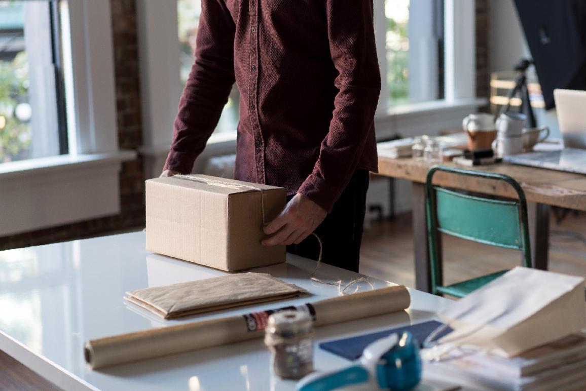 osoba preväzuje balík na stole v ateliéri