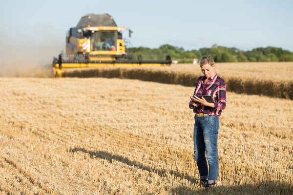 Photo of a women standing on a field with a tractor in the background