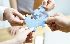 Different people bring together puzzle pieces