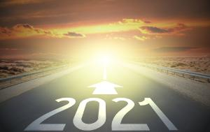 Road leading to horizon with sunrise, 2021 and arrow painted on it
