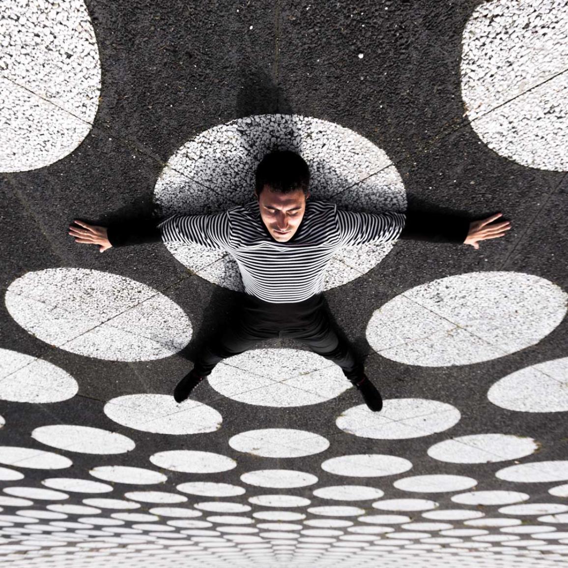 Homem deitado no chão de um parque infantil ou numa estrada com uma camisola às riscas (estlo passadeira)