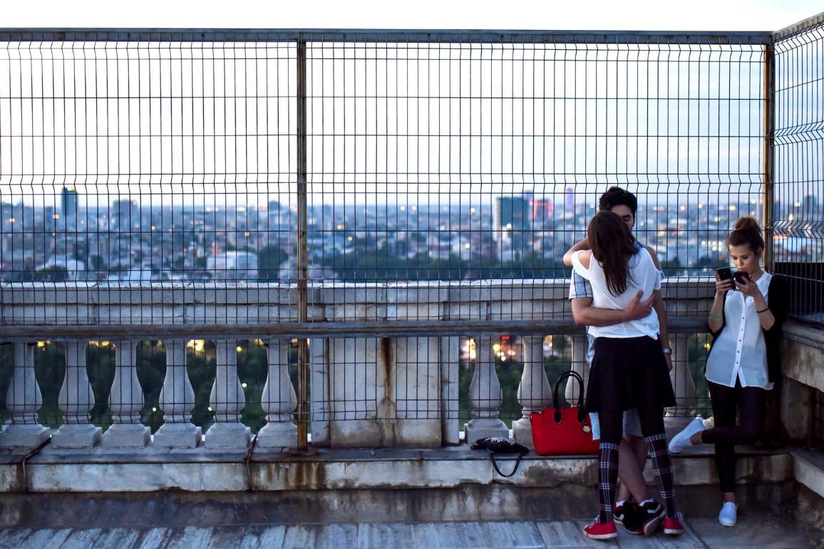Um casal jovem beija-se com vista para o centro da cidade
