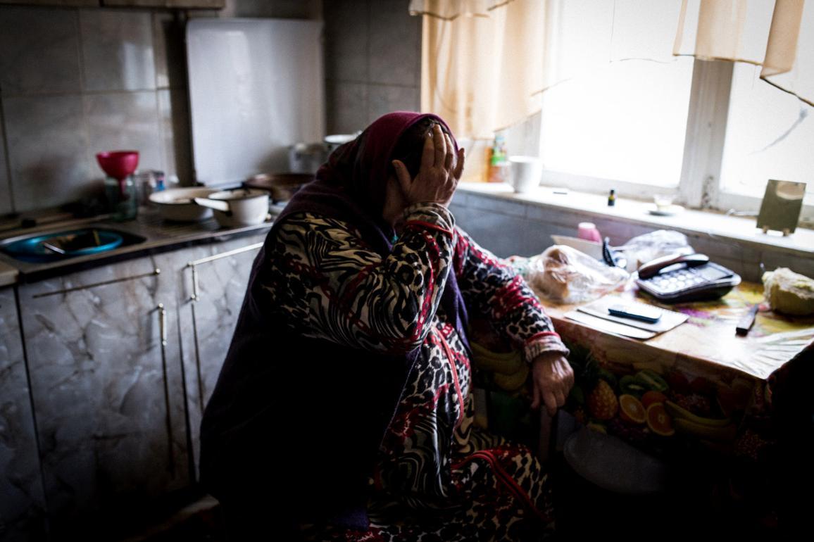 Senhora sentada numa cozinha com mão na cabeça em tom de desespero.