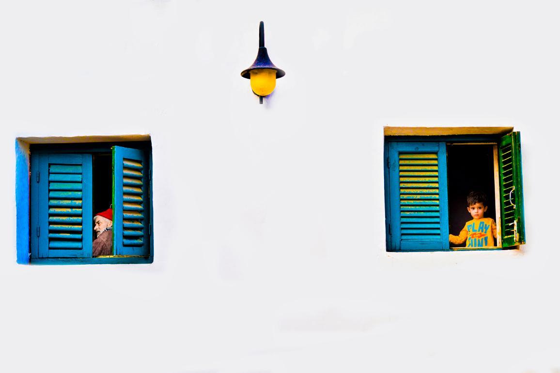 farebné okná na bielom dome, v jednom je starý muž, v druhom malý chlapec