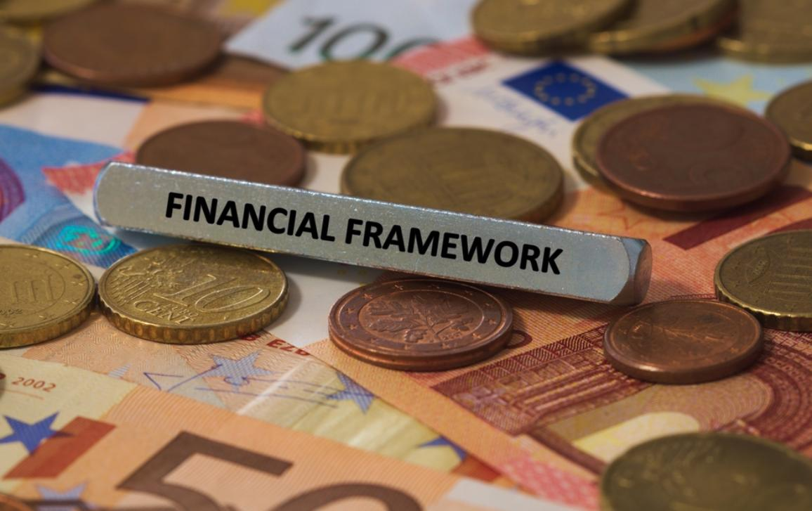 Metal bar saying 'Financial Framework' on a background of euro coins and bills