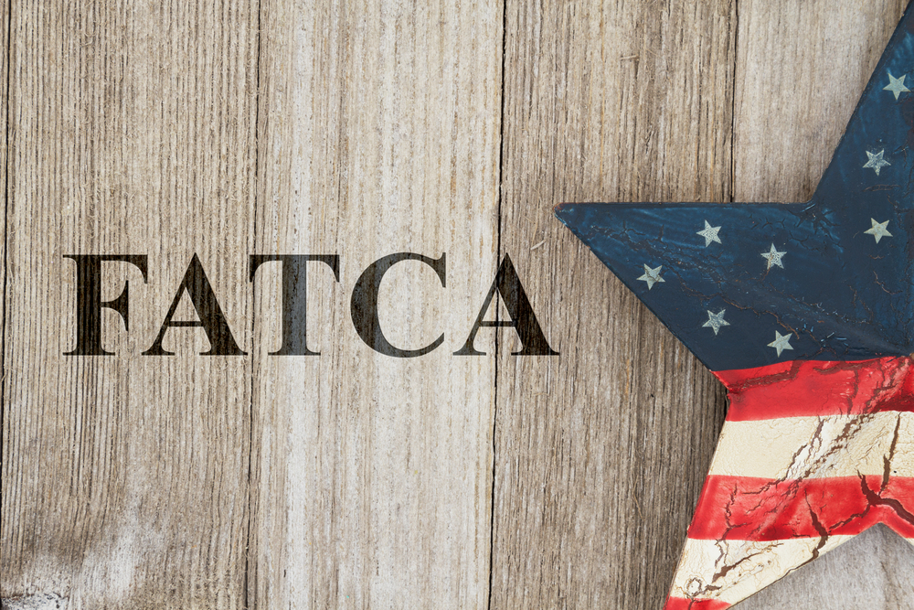 Complying with the US Foreign Account Tax Compliance Act, USA patriotic old flag on a stars with weathered wood background with text FATCA