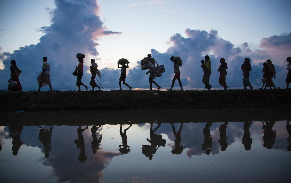 Silhouette of refugees walking on horizon along river