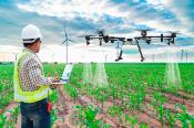 Drone above a field and man with computer
