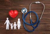 Paper silhouette of family, stethoscope and heart on wooden background.