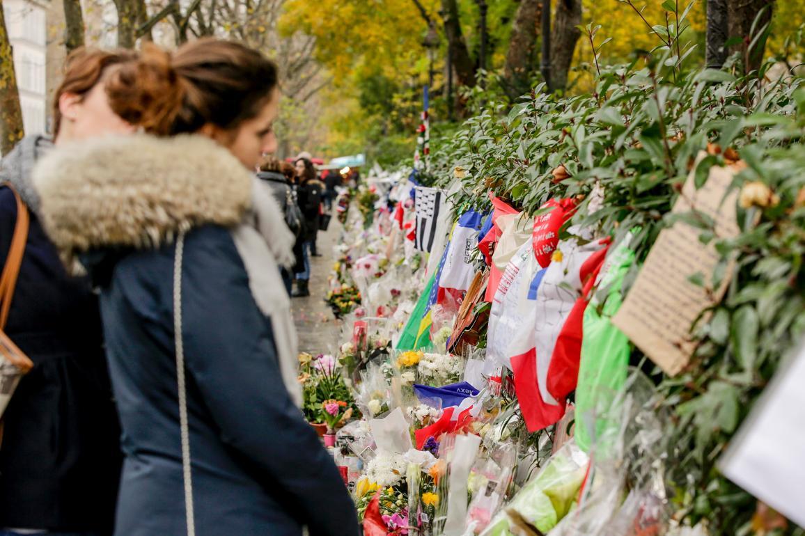 Das Bild zeigt trauernde Menschen vor einer Gedenkmauer mit Blumen