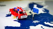 Mini Cooper car with Union Jack flag and Brexit words over an UE map and flag.