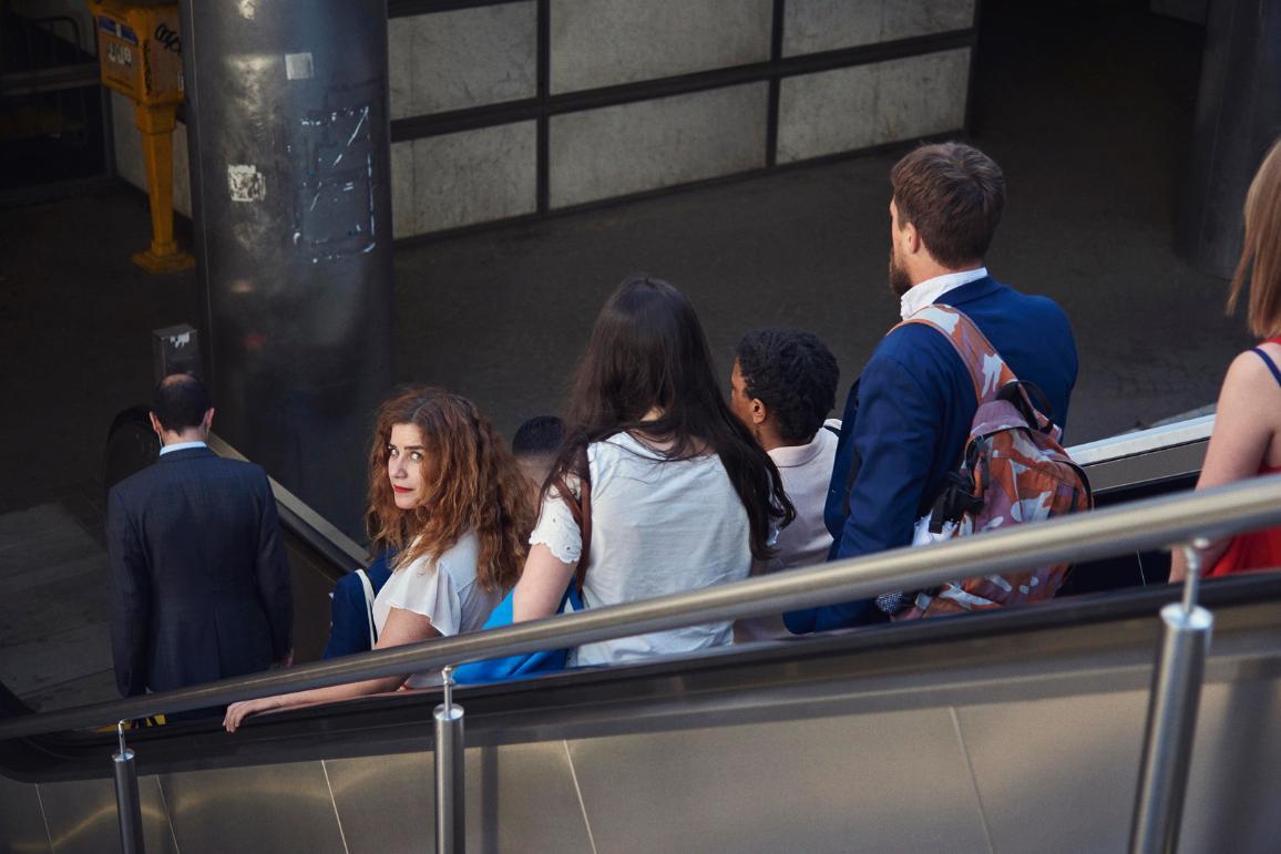 Млада жена поглежда назад, докато се вози с други хора на ескалатор