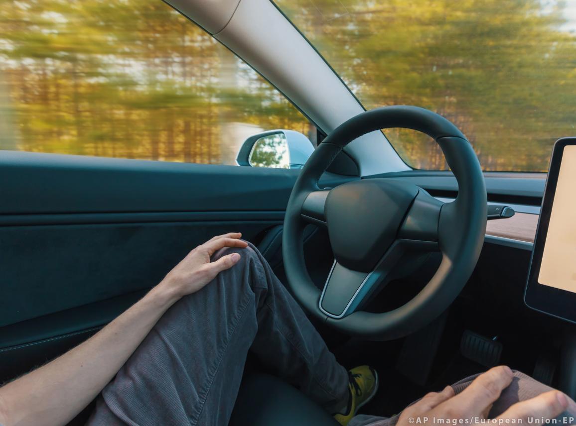 Person using a car in autopilot mode hands free ©AP images/European Union-EP