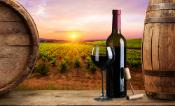 A wine bottle and red wine glass with bottle opener on a table between two wine barrels with a view on a wine yard in Tuscany, Italy and a sunset warm light in the background