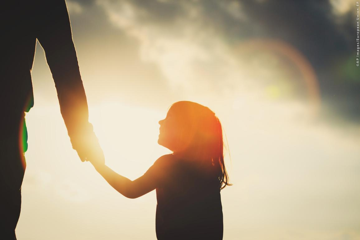 Silhouette of little girl holding parent hand at sunset ©AP images/European Union - EP