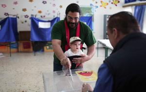 Man casting his vote while holding his child