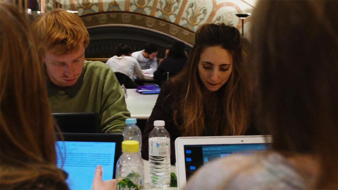 mladí ľudia sedia za stolom a píšu na laptopoch
