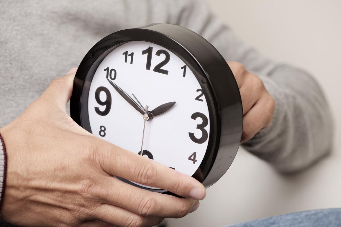 Man adjusting the time of a clock