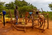 Children and adults pumping water from a water well in Africa
