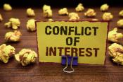 Handwriting text writing Conflict Of Interest. Yellow sticky card clipped text notice crumpled paper balls wood table