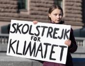 "Greta Thunberg, the 16-year-old climate activist from Sweden holding a poster with ""school strike for the climate"" slogan"