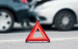 Car accident and a red triangle warning sign on the road