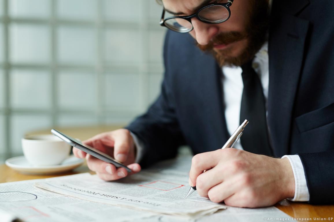 Una persona busca en la página de ofertas laborales de un periódico © AP Images/European Union - EP.